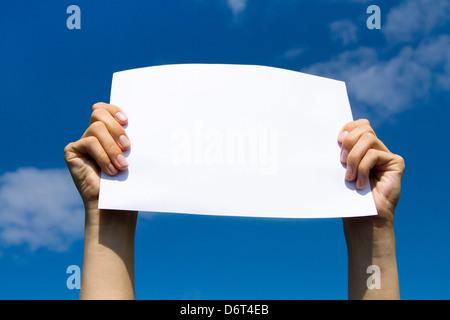 Pagina vuota in mani sul cielo blu sullo sfondo Foto Stock