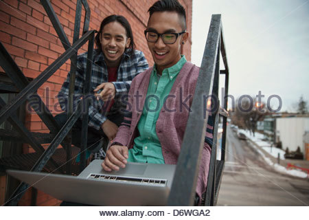 Happy amici maschio utilizzando laptop sul fuoco scala di uscita Foto Stock
