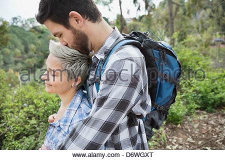 Vista laterale dell'uomo donna baciare sulla testa nella foresta Foto Stock