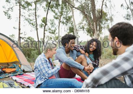 Gli amici di ridere mentre fuori camping insieme Foto Stock