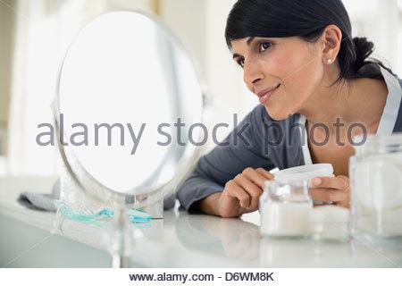 Bella donna crema di azienda bottiglia mentre cercando in specchio da toeletta Foto Stock