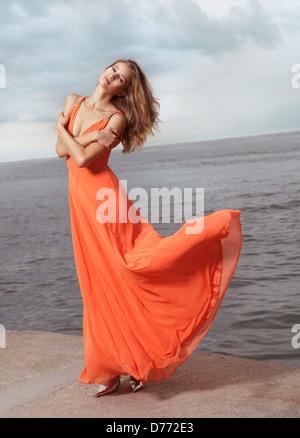 Bella giovane donna in arancione abiti estivi battenti nel vento in piedi su una riva del mare Foto Stock