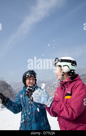 Giovane uomo e donna giocare nella neve nella stazione sciistica Foto Stock