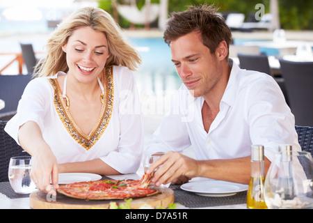Giovane godendo di pasto in un ristorante esterno Foto Stock