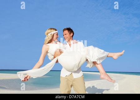 Lo sposo che trasportano Sposa bella spiaggia Wedding Foto Stock