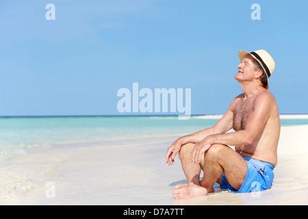 Senior uomo godendo di vacanze in spiaggia Foto Stock
