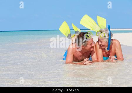 Coppia senior con boccagli godendo di vacanze in spiaggia Foto Stock