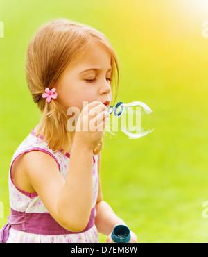 Closeup ritratto di simpatici baby girl soffiando bolle di sapone nella primavera del parco, avendo divertimento Foto Stock