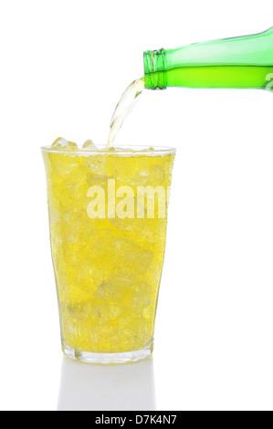 Una bottiglia di limone soda calce versando in un bicchiere riempito con cubetti di ghiaccio su uno sfondo bianco.
