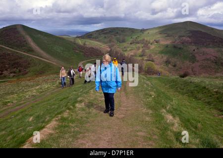 Una donna e un gruppo di persone che camminano nella Malvern Hills, worcestershire, Foto Stock
