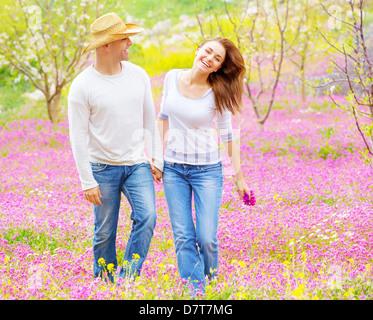 Bella coppia felice godendo di primavera la natura, ridendo e divertimento all'aperto, camminando su purple floral Foto Stock