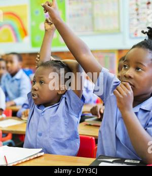 Gli studenti alzando le mani in classe Foto Stock