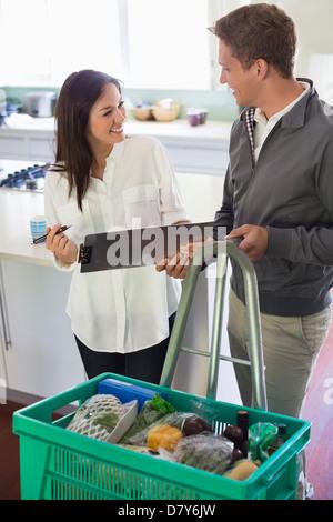 La donna la firma per la consegna in cucina Foto Stock