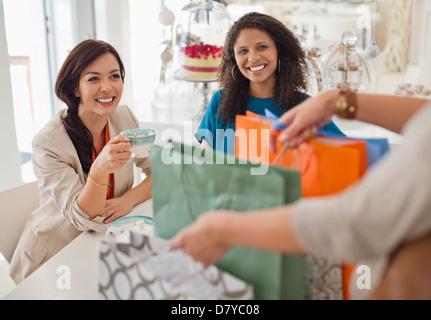La donna che mostra gli amici delle borse per lo shopping Foto Stock