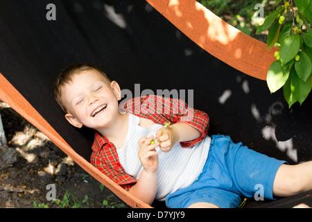 Ridendo little boy stare sdraiato sulla schiena in una amaca sotto un albero ombroso godendo la soleggiata primavera Foto Stock