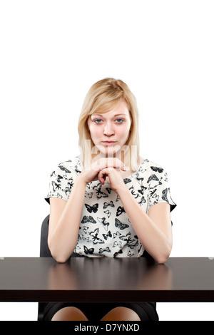 Bella donna bionda in abbigliamento business guarda fiducioso al banco contro uno sfondo bianco Foto Stock