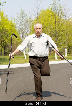 Anziani disabili uomo che ha subito un al di sopra del ginocchio amputazione su una gamba in piedi in una strada Foto Stock