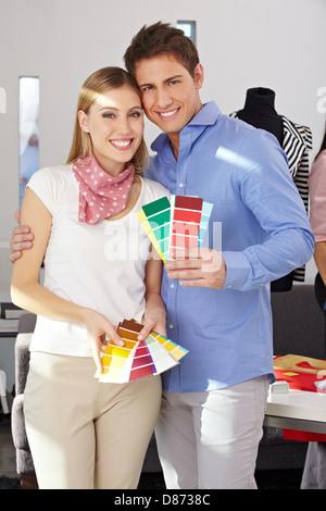 Giovane coppia felice in piedi con i campioni di colori Ventilatore in studio Foto Stock