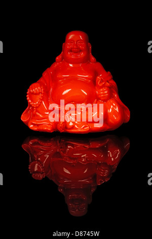 Red buddha sorridente su sfondo nero, close up Foto Stock