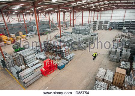 Lavoratori a piedi attraverso il magazzino con tubi di acciaio e finito di barriere di sicurezza Foto Stock