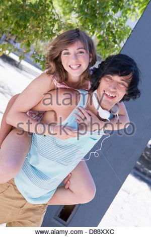 Ritratto di giovane sorridente giovane piggybacking e ascolto di musica digitale compressa Foto Stock
