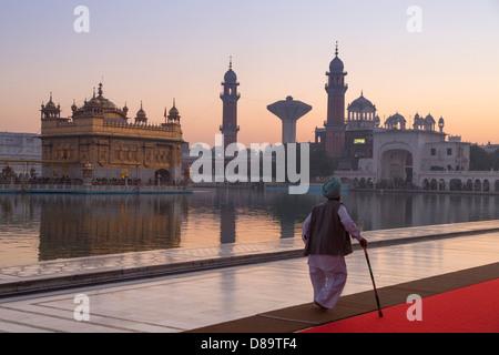 India, Punjab, Amritsar. Tempio d'oro uomo anziano in tradizionale costume sikh camminare al complesso Foto Stock