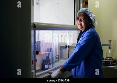Il centro di ricerche mediche e alle attrezzature industriali, donna pulizia tubi di test in laboratorio Foto Stock