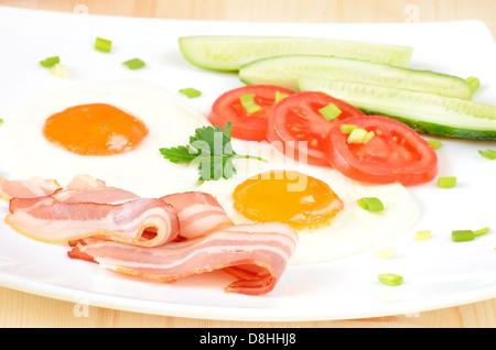 La prima colazione con pancetta, uova fritte e fette di pomodoro su piastra bianca Foto Stock