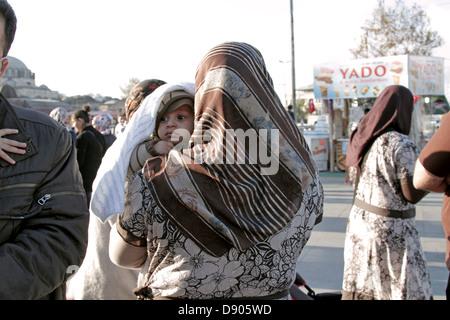 La donna musulmana che porta il bambino EMINONU Istanbul Turchia 11 Novembre 2012 Foto Stock