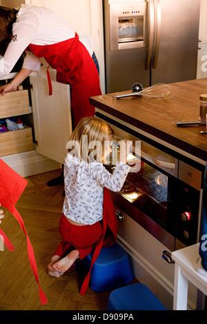 Una ragazza seduta sul pavimento cercando in un forno. Foto Stock