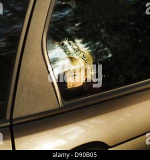 Una ragazza scandinavo con una corona in suoi capelli guardando fuori dal finestrino di un'automobile, Svezia.