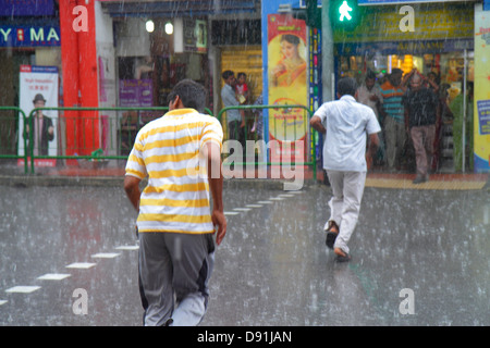 Singapore Little India Serangoon Road uomo asiatico in funzione pioggia pioggia meteo monsone clima Foto Stock