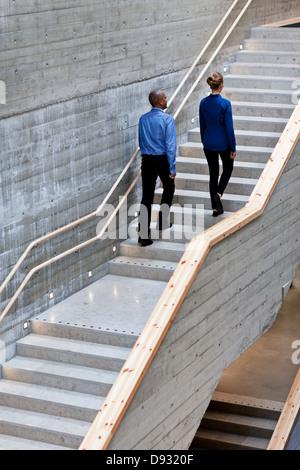 Uomo e donna che cammina su scale Foto Stock