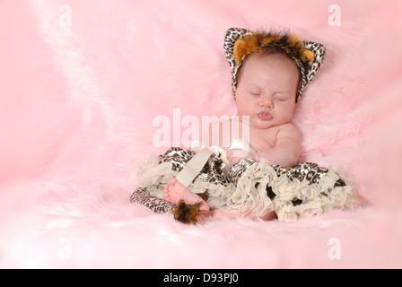 Neonato vestito come un gatto su sfondo rosa - 2 mesi di età Foto Stock