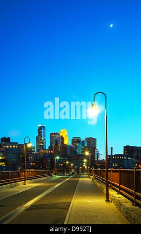Il centro di Minneapolis, Minnesota di notte tempo visto come dal famoso arco in pietra bridge