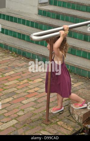 Ragazza giovane indossando abiti estivi e jandals appoggiata alla ringhiera scale Foto Stock