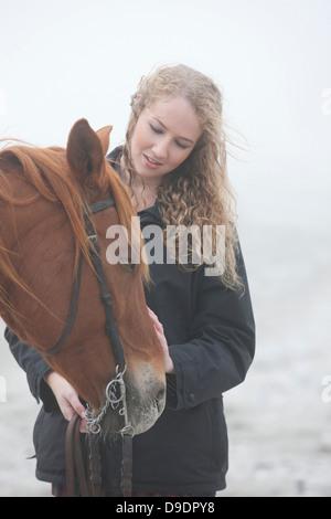 La donna a cavallo sulla spiaggia Foto Stock