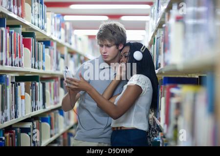 Gli studenti Ascolto di mp3 player nella libreria Foto Stock