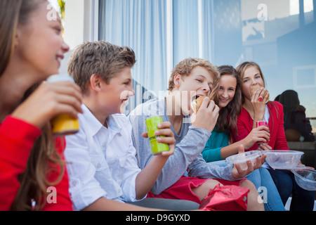 Gli amici sorseggiando un fast food insieme Foto Stock