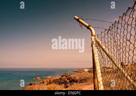 Il montante d'angolo del filo di pollo recinto con rotture di trefoli di filo spinato sopra, sulla costa, vicino Foto Stock