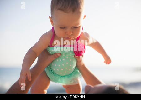 Sollevamento donna bambina indossando il costume da bagno Foto Stock