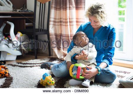 Donna che gioca con la sua adozione baby boy Foto Stock