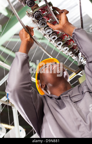 African American tessile tecnico industriale riparazione macchina di tessitura Foto Stock