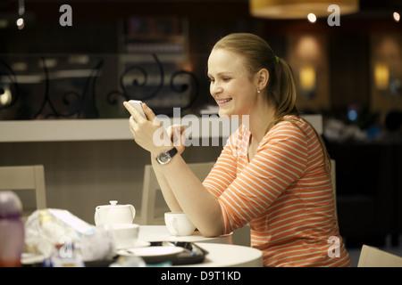 Giovane donna chattare su smartphone nel cafe. Foto Stock