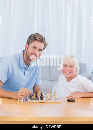 Padre sorridente giocando a scacchi con suo figlio Foto Stock