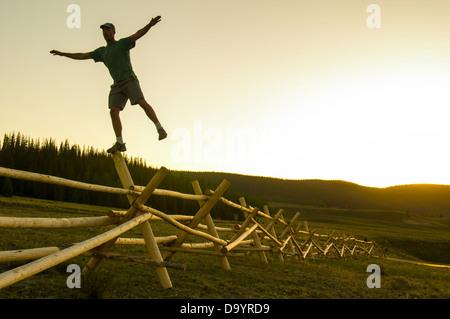 Un uomo in equilibrio su una recinzione al tramonto, Rio Grande Foresta Nazionale, Creede, Colorado(silhouette). Foto Stock