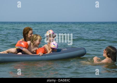 Joyfull bambini che giocano su un materasso gonfiabile nel Mar Baltico Foto Stock