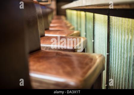 Una fila di pelle marrone sgabello da bar sedie allineate accanto a