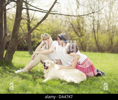 Famiglia seduto in posizione di parcheggio con il cane Foto Stock