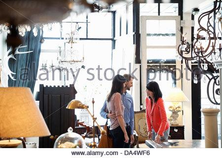 Femmina proprietario di affari ad aiutare i clienti nel negozio di mobili Foto Stock